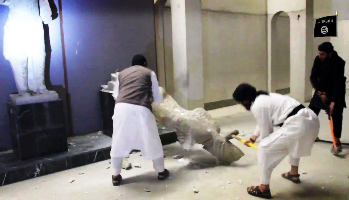 In this image made from a video posted on a social media account affiliated with the Islamic State group on Feb. 26, 2015, militants take sledgehammers to an ancient artifact in the Ninevah Museum in Mosul, Iraq. (AP Photo via militant social media account)