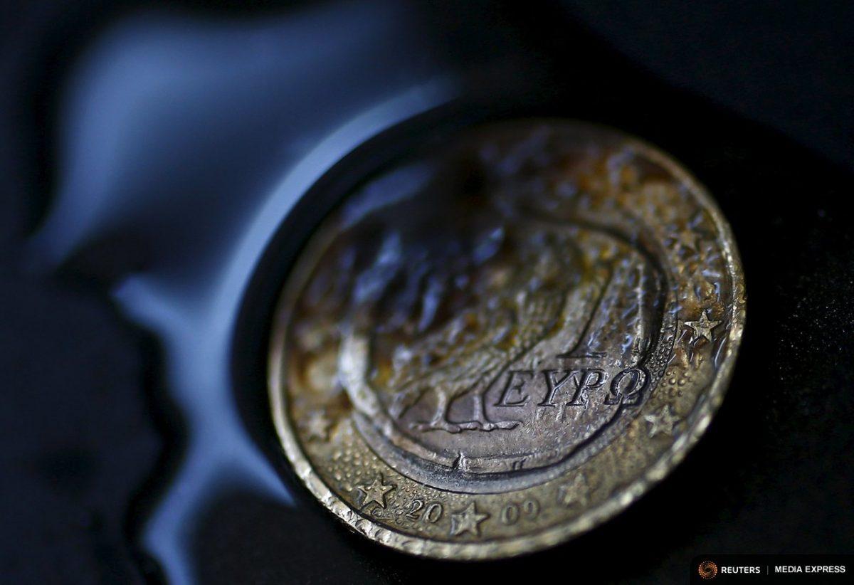 A one Euro coin with a Greek owl is seen burning. (REUTERS/Kai Pfaffenbach)