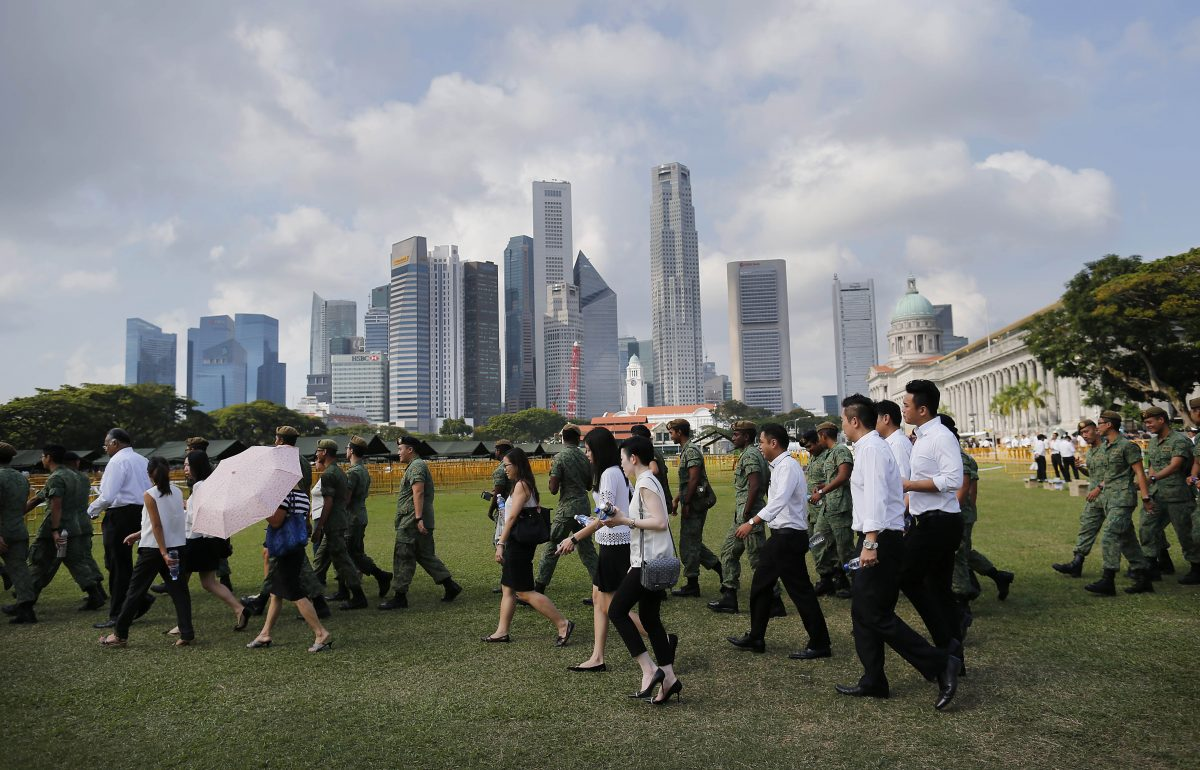 Members of the public wait in line with the financial skyline of Singapore in the background, to pay their respects to the late Lee Kuan Yew at the Parliament House where he will lie in state for four days, Thursday, March 26, 2015, in Singapore. Lee, 91, died Monday at Singapore General Hospital after more than a month of battling severe pneumonia. The government declared a week of mourning for the leader who is credited with transforming the resource-poor island into a wealthy finance and trade hub with low crime and corruption in a region saddled with graft, instability and poverty. (AP Photo/Wong Maye-E)