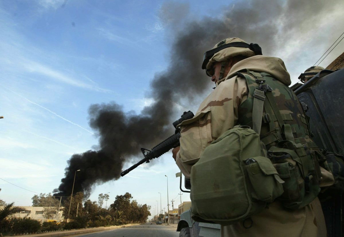A U.S. soldier stands on the ready in a convoy as smokes billows from a truck loaded with explosive was destroyed in Najaf, Iraq, April 2, 2003. (AP Photo/Jean-Marc Bouju)