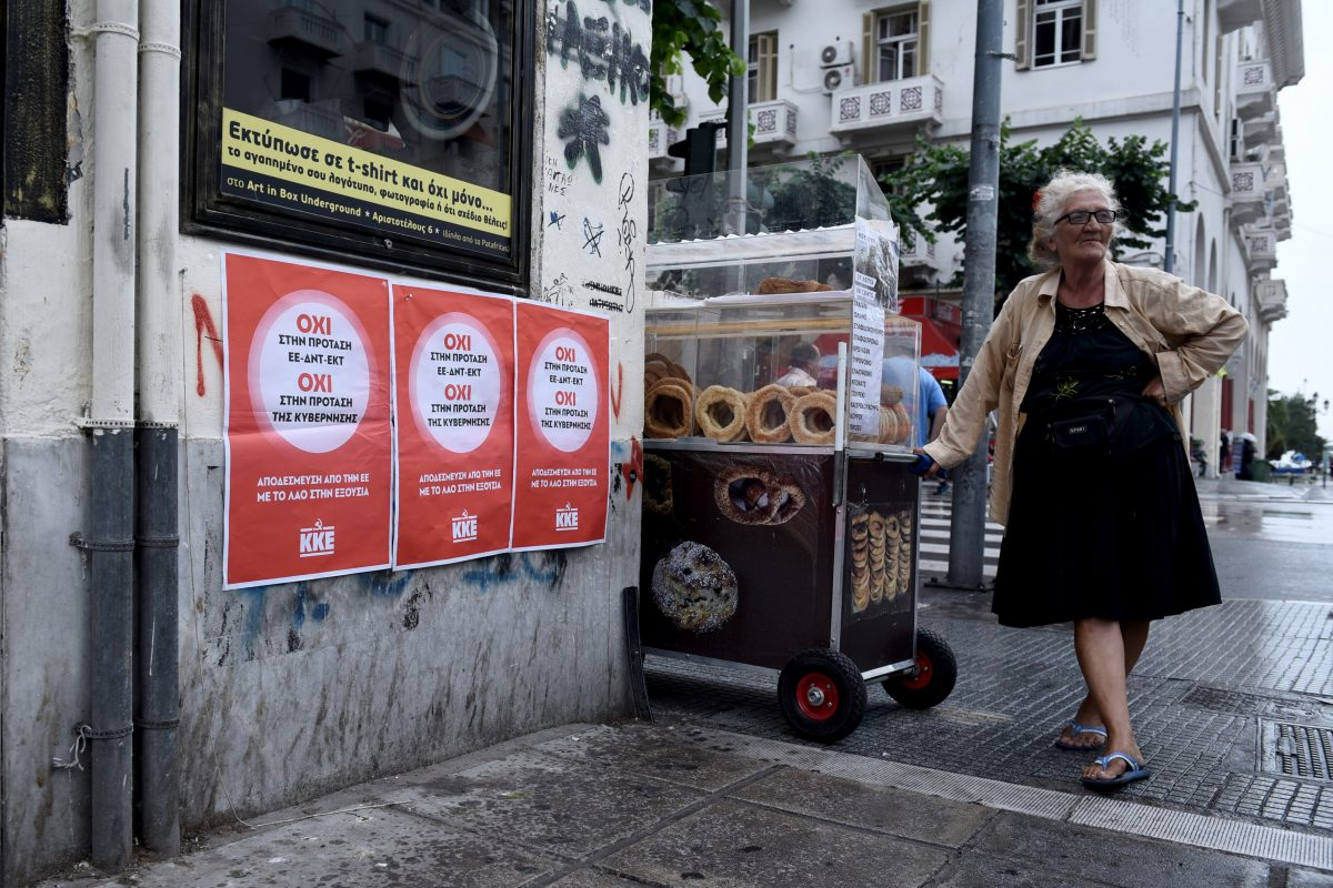 An elderly woman sells bread next to posters reading ''NO to EU, IMF, ECB proposal'' in the Greek city of Thessaloniki, Wednesday, July 1, 2015. (AP Photo/Giannis Papanikos)