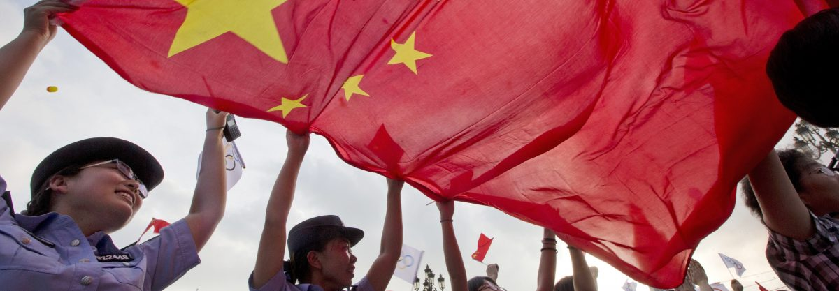 Chinese policewomen wave a Chinese national flag to celebrate as Beijing is announced as the host city for the 2022 Winter Olympics at the ski resort region of Chongli where the Nordic skiing, ski jumping, and other outdoor Olympic events will be held in northern China's Hebei province Friday, July 31, 2015. Beijing was selected Friday to host the 2022 Winter Olympics, becoming the first city awarded both the winter and summer games. (AP Photo/Ng Han Guan)