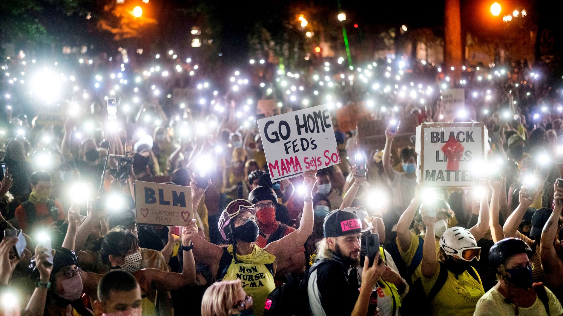 Black Lives Matter protesters hold their phones aloft in Portland, Oregon, 20 July 2020